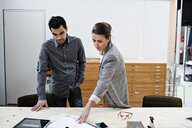 Confident male and female business colleagues discussing over documents at table in office - MASF07663