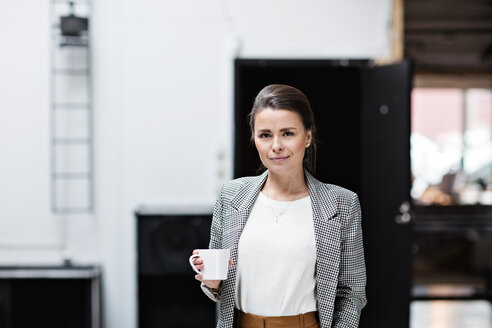 Portrait of beautiful smiling businesswoman having coffee while standing at office - MASF07666