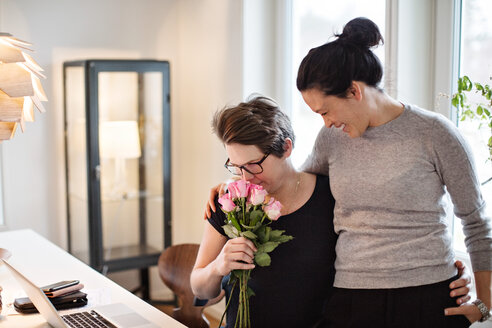 Smiling woman looking at girlfriend smelling pink roses at home - MASF07726