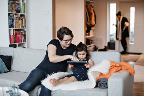 Mother showing digital tablet to daughter while sitting on sofa at home - MASF07732