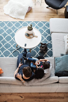 Directly above shot of lesbian couple sitting with daughter on sofa by dog in living room at home - MASF07750