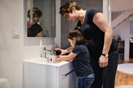 Woman assisting daughter in washing hands at sink in house - MASF07753