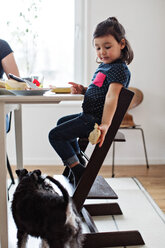 Girl giving bread to dog while sitting at table in house - MASF07780