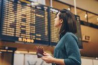 Side view of businesswoman looking at arrival departure board in airport - MASF07798