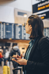 Mid adult businesswoman using mobile phone while standing in airport - MASF07801