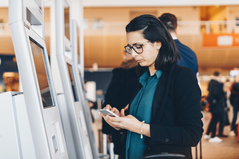 Businesswoman using mobile phone by automated check-in machine in airport - MASF07807