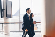 Side view of businessman and businesswoman walking in airport terminal - MASF07810