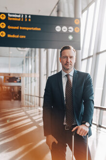 Portrait of confident mature businessman standing in airport terminal - MASF07813