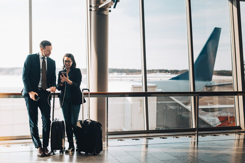 Full length of business couple with luggage using mobile phone in airport - MASF07819
