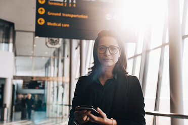 Portrait of confident businesswoman holding mobile phone and passport in airport terminal - MASF07822