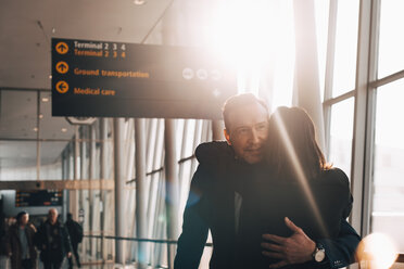 Business couple embracing in airport terminal - MASF07825