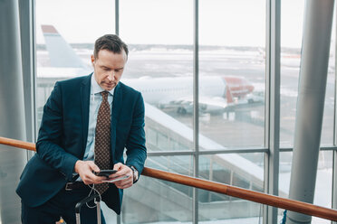 Businessman using mobile phone while leaning on railing in airport - MASF07846