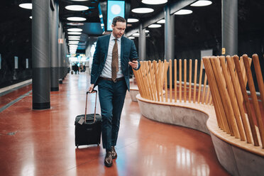 Full length of businessman with luggage and mobile phone walking in railroad platform - MASF07852