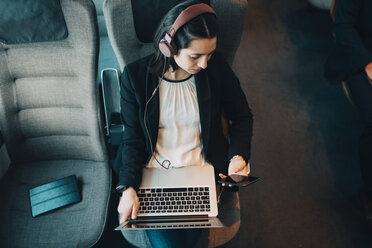High angle view of businesswoman using various technologies while traveling in train - MASF07855