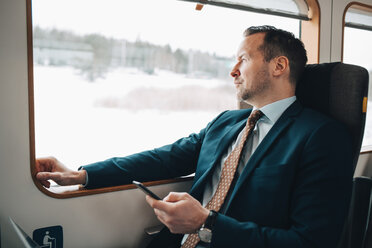 Thoughtful businessman holding mobile phone while traveling in train - MASF07858