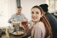 Smiling girl having drink while sitting with family at table during party - MASF07915