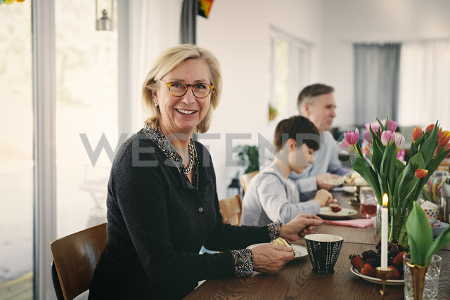 Portrait of smiling grandmother sitting with family at table during party - MASF07918 - Maskot/Westend61