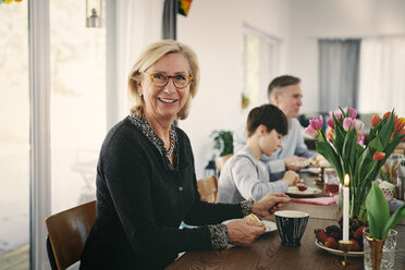 Portrait of smiling grandmother sitting with family at table during party - MASF07918