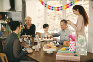 Multi-generation family enjoying birthday cake at table during party - MASF07921