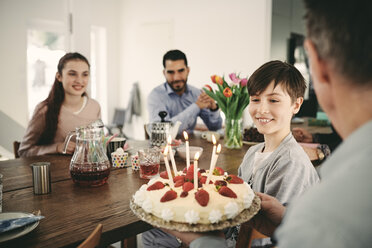 Boy looking at birthday cake while sitting with family at home - MASF07924