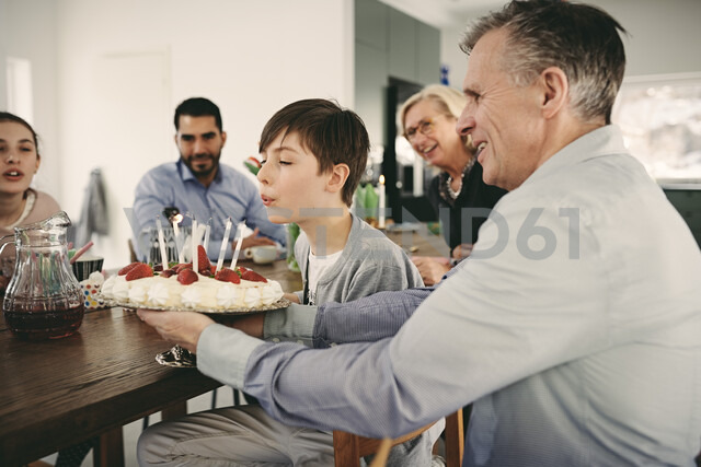 Boy blowing candles on birthday cake while sitting with family during party - MASF07927