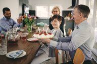 Smiling boy with grandparents and father with birthday cake at table - MASF07930