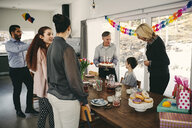 Grandfather showing birthday cake to boy while happy family enjoying at party - MASF07933