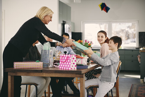Grandmother giving gift to boy sitting with family at dining table - MASF07936