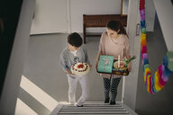 High angle view of siblings carrying birthday cake and gift box while climbing up steps at home - MASF07939
