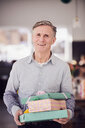 Portrait of senior man holding stacked gift boxes while standing at home - MASF07942
