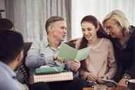 Grandfather reading greeting card to happy family while sitting on sofa at home - MASF07945