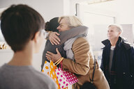 Senior woman embracing daughter while standing at doorway with family - MASF07951