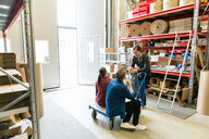 Male and female coworkers discussing during coffee break in warehouse - MASF07954