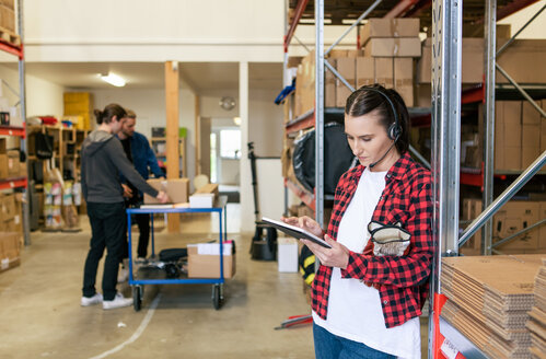 Female manual worker using digital tablet while standing by rack with colleagues working in background - MASF07957