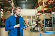 Confident manual worker wearing headphones while using digital tablet in warehouse - MASF07960