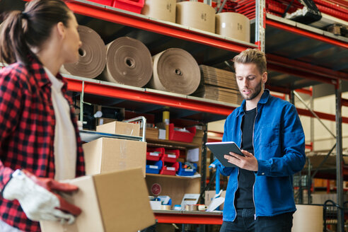 Male worker using digital tablet while woman holding cardboard box in warehouse - MASF07963