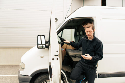 Manual worker using mobile phone while standing by delivery van - MASF07975