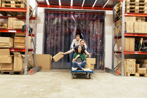 Male and female coworkers enjoying while working at warehouse - MASF07984