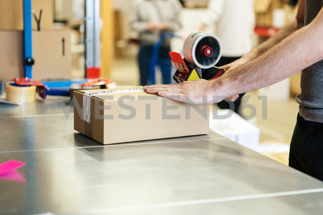 Midsection of man packing box in distribution warehouse - MASF07996