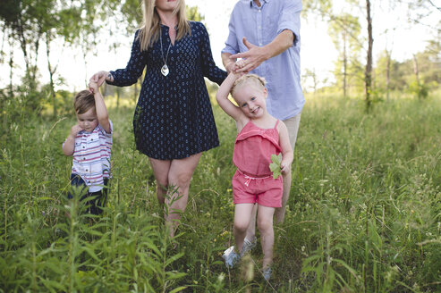 Mid adult parents strolling in meadow boy and girl - CUF20906