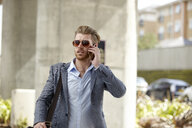 Young businessman wearing sunglasses talking on smartphone outside office, London, UK - CUF21008