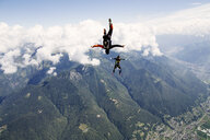Freestyle skydiving team training together. One man  performing air-ballet, another jumper is filming with video camera on helmet, Locarno, Tessin, Switzerland - CUF21011
