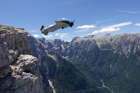 Wingsuit BASE jumper is flying from a cliff Italian Alps, Alleghe, Belluno, Italy - CUF21014