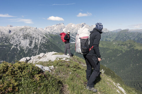 Two wingsuit BASE jumpers walking to the exit spot at Col di Pra, Italian Alps, Alleghe, Belluno, Italy - CUF21017