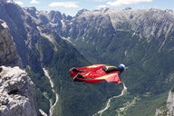 Wingsuit BASE jumper flying along cliff side and down the valley, Italian Alps, Alleghe, Belluno, Italy - CUF21023