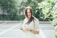 Portrait of young woman with freckles and long red hair holding smartphone in parking lot - CUF21212