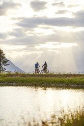 Austria, Tyrol, Mountainbikers in the evening light - CVF00645