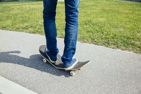 Man standing on broken skateboard - AIF00503