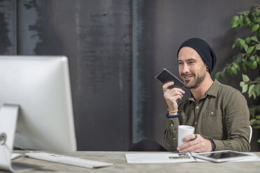 Smiling young man with cell phone at desk in office - ZEF15525