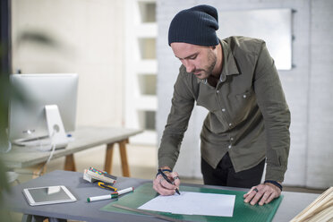 Young man taking notes at desk in office - ZEF15540